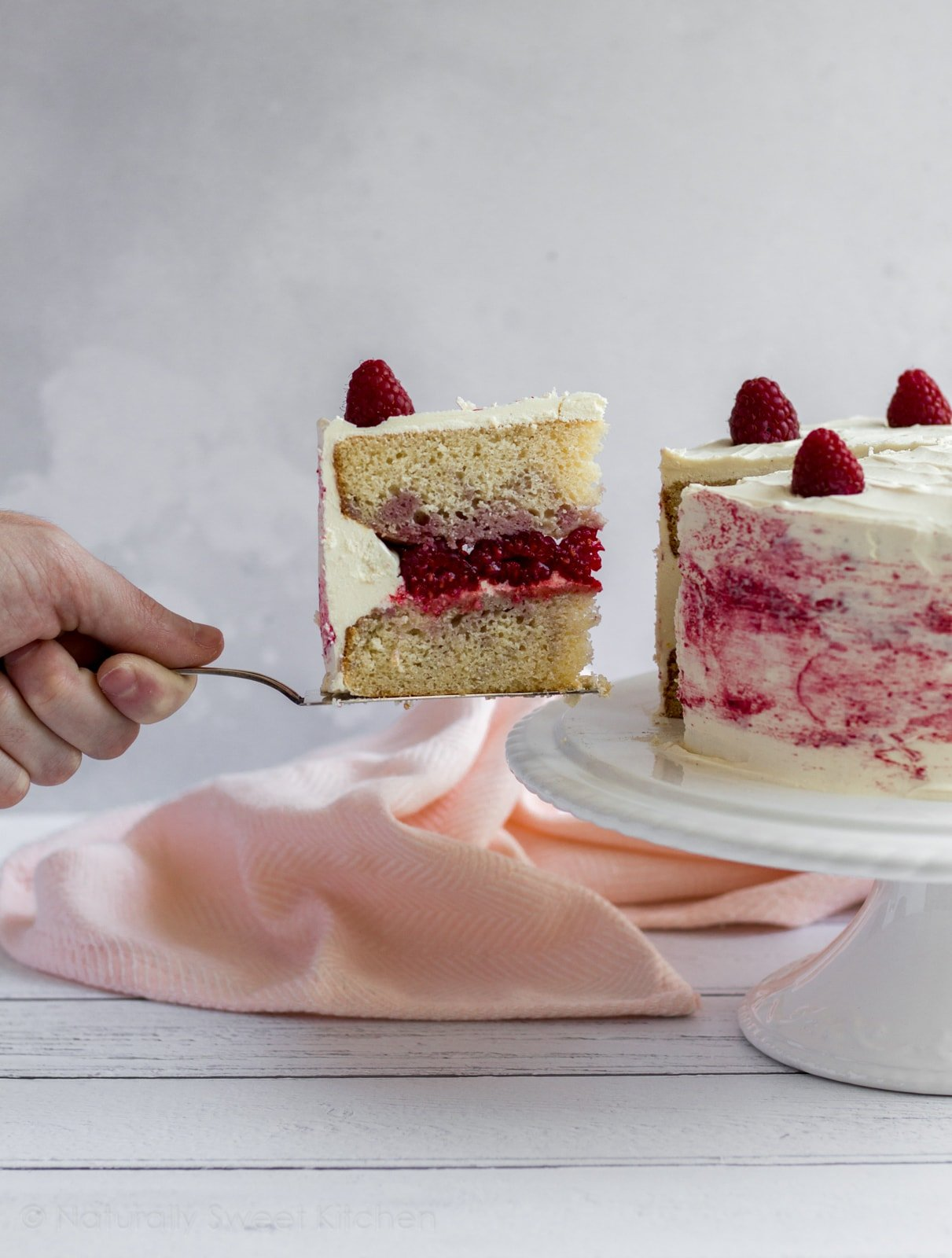 This modern, elegant White Chocolate Raspberry Ripple Cake features velvety white chocolate buttercream, raspberry swirl vanilla cake and fresh raspberries. #cake #raspberry #refinedsugarfree
