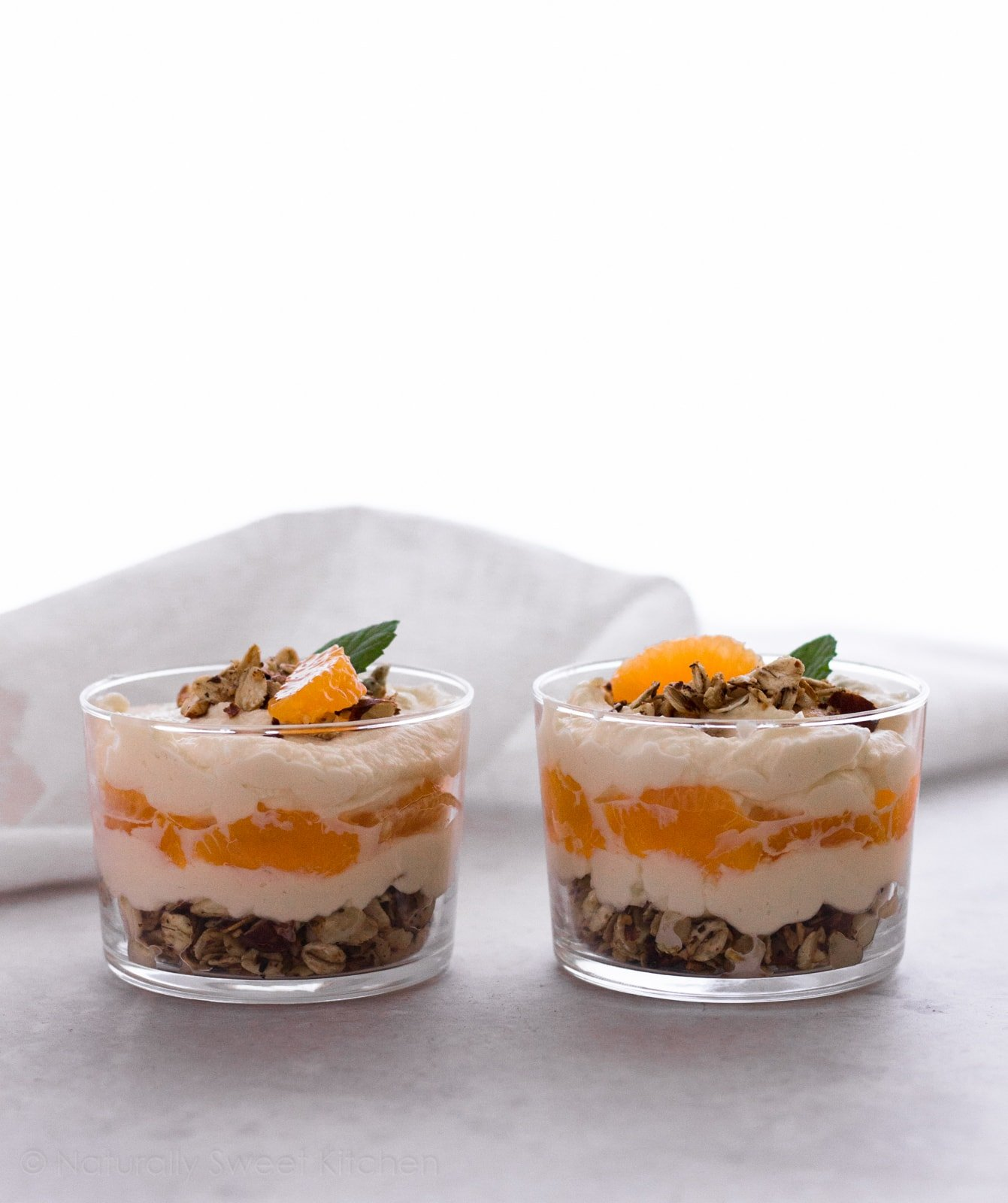 A natural, whole foods twist on a childhood classic, these light and decadent Orange Creamsicle Parfaits are ready in minutes. A perfect quick and easy summer dessert. | Naturally Sweet Kitchen | Summer Dessert | Quick and Easy Dessert | Orange Parfait #dessertrecipe #orangecreamsicle
