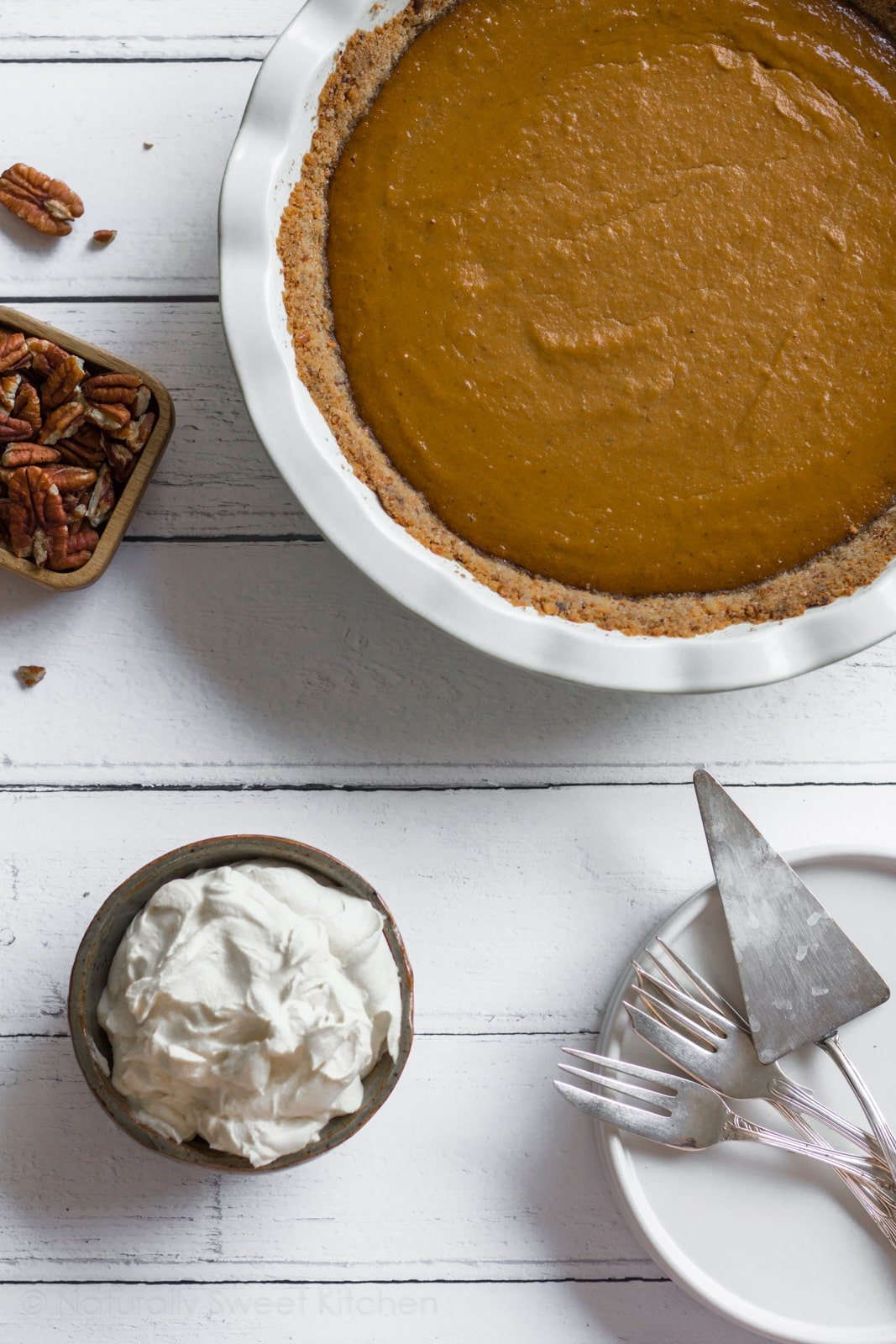 Enjoy a slice of this refined sugar free Pumpkin Pie with a Pecan Pretzel Crust after your Thanksgiving feast. Your guests will love the traditional sweet filling combined with the unconventional salty crunch. | naturallysweetkitchen.com #pumpkinpie #pretzelcrust