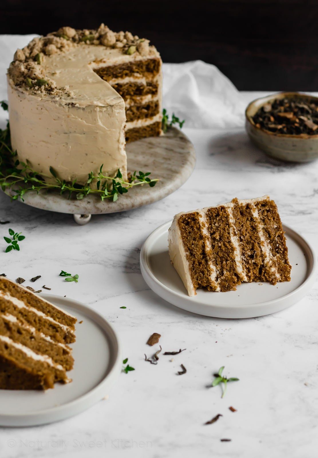 This Apple Chai Cake with refined sugar free Swiss Meringue Maple Frosting is filled with tart apples, heady, warming chai tea spices, and is incredibly moist. Get the recipe and more refined sugar free cakes at naturallysweetkitchen.com #cakerecipe #chaicake #chaitea #applecake #maplefrosting #refinedsugarfree