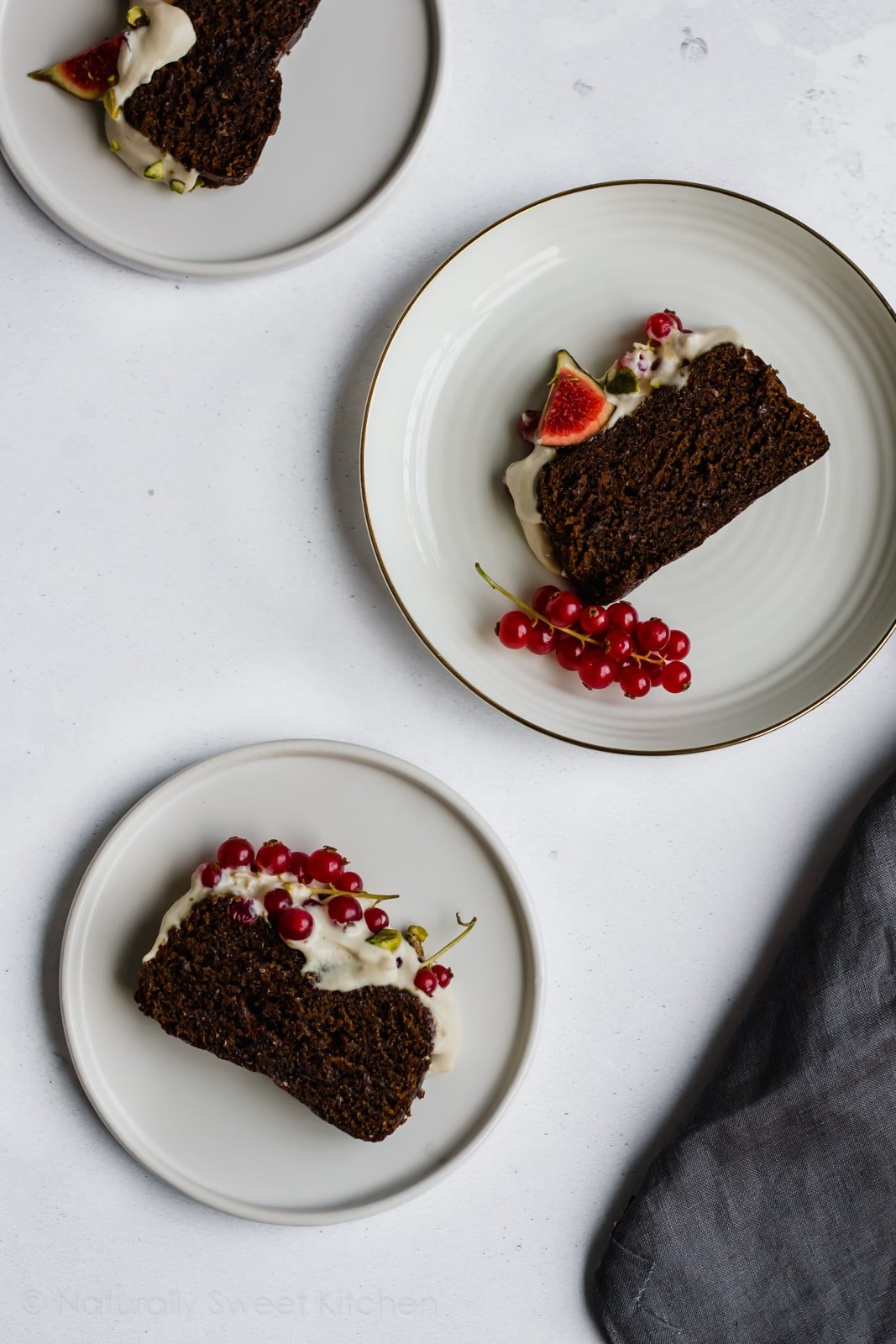 This easy gingerbread cake is made in a loaf tin and completely vegan. Topped with a cashew cream cheese frosting, winter fruit, and pistachios, this is the best Christmas cake recipe. Visit naturallysweetkitchen.com for the recipe and other refined sugar free cakes. #naturallysweetkitchen #refinedsugarfree #vegan #vegancake #gingerbread #gingerbreadcake #christmasrecipes