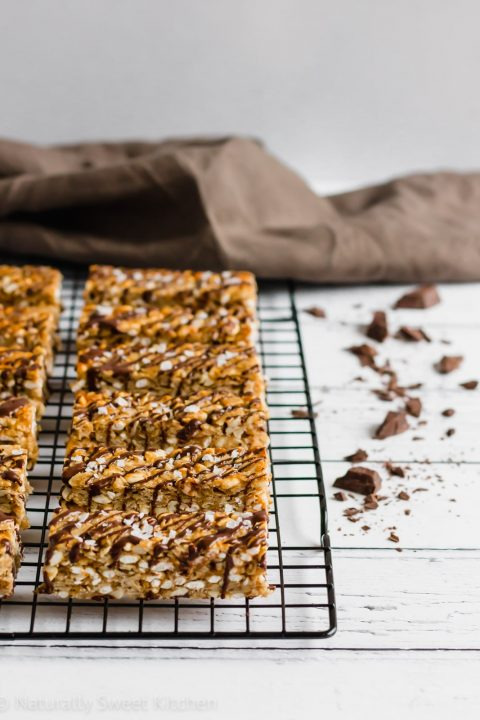 These homemade peanut butter granola bars are simply the best. Made with all natural ingredients and no refined sugar, these are the perfect chewy granola bar to pop into a lunch box. You'll love the drizzle of dark chocolate and the sprinkle of salt! Get the recipe at naturallysweetkitchen.com #naturallysweetkitchen #refinedsugarfree #baking #wholefoods #rolledoats #granolabars #chocolate #peanutbutter #glutenfree #easyrecipe