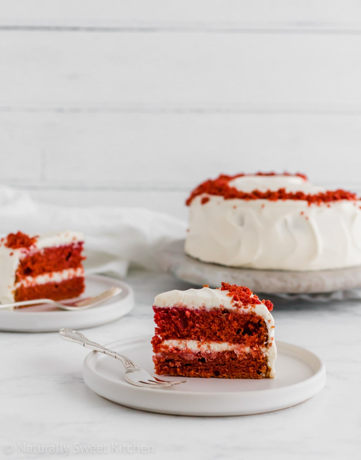 This moist natural red velvet cake recipe features two pint-sized cake layers and an easy cream cheese frosting without powdered sugar! Get the recipe for this refined sugar free cake at naturallysweetkitchen.com. #refinedsugarfree #naturallysweetkitchen #baking #redvelvet #redvelvetcake #Valentinesdessert #dessert #foodphotography #cakerecipe #cake