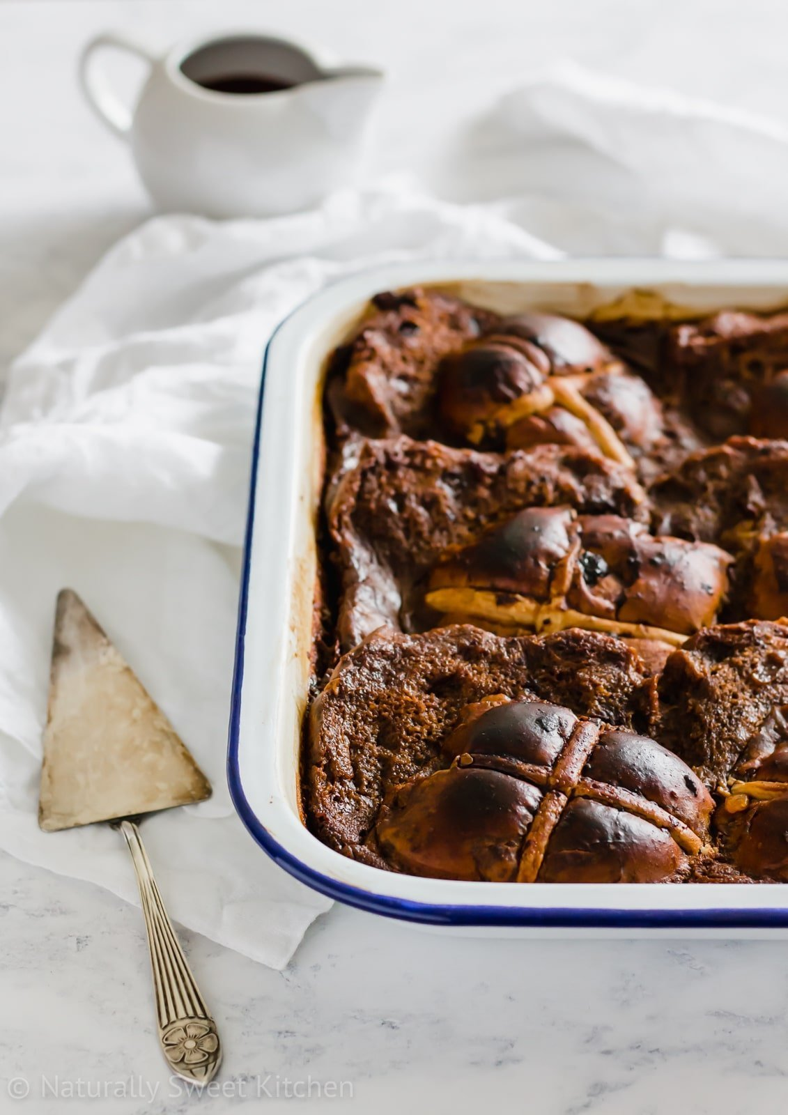 This rich Chocolate Hot Cross Bun Pudding recipe is the best way to use up stale hot cross buns for Easter dessert! A delicious refined sugar free twist on the classic bread and butter pudding. Visit naturallysweetkitchen.com for this recipe and more sugar free desserts. #hotcrossbuns #naturallysweetkitchen #chocolate #Easterdessert