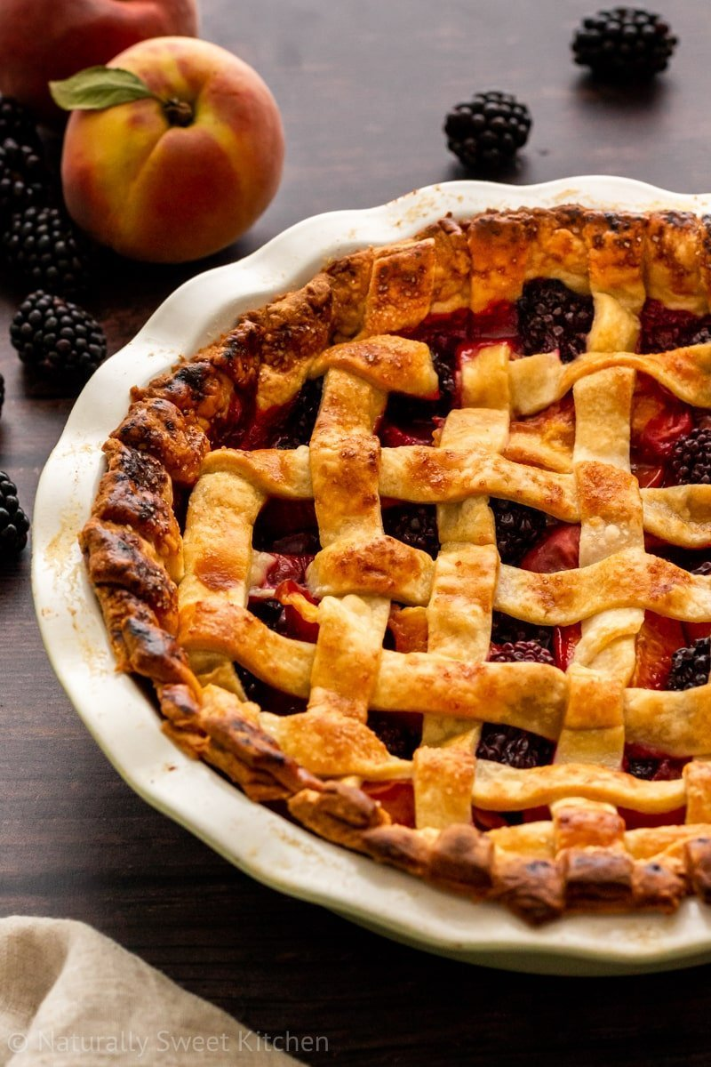 Food photography shot of a lattice crust refined sugar free peach and blackberry pie.