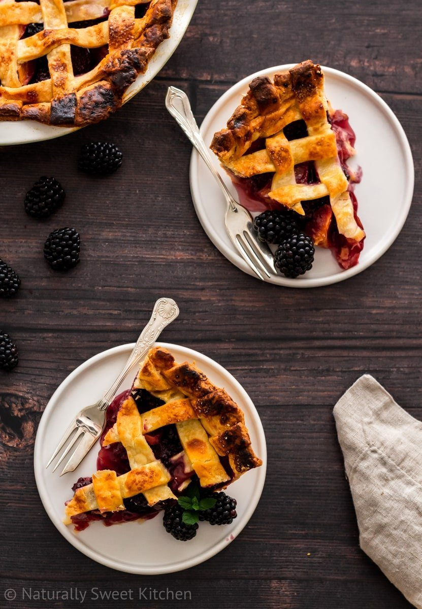 Above head shot of slices of fresh fruit pie and blackberries.