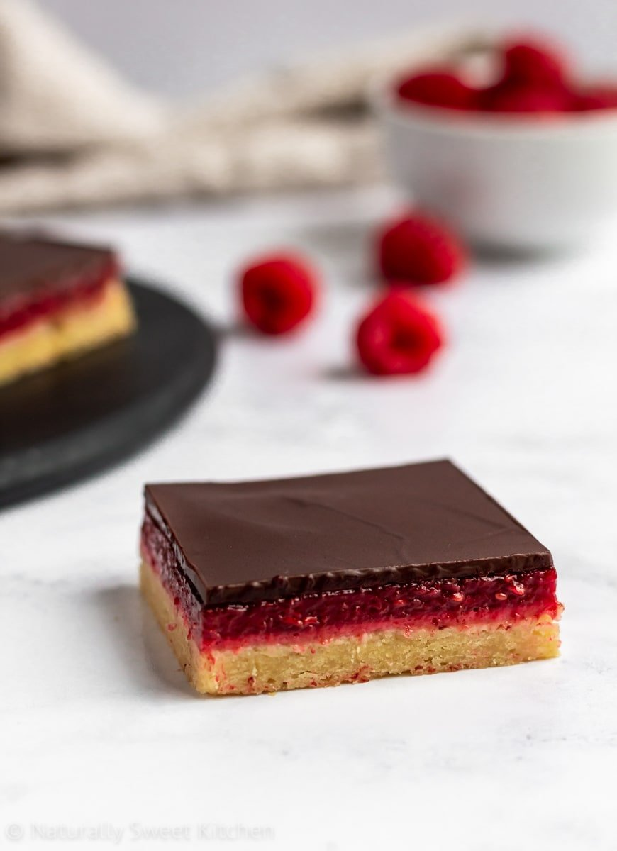 An image of chocolate raspberry bars featuring layers of shortbread, homemade raspberry jelly, and dark chocolate.