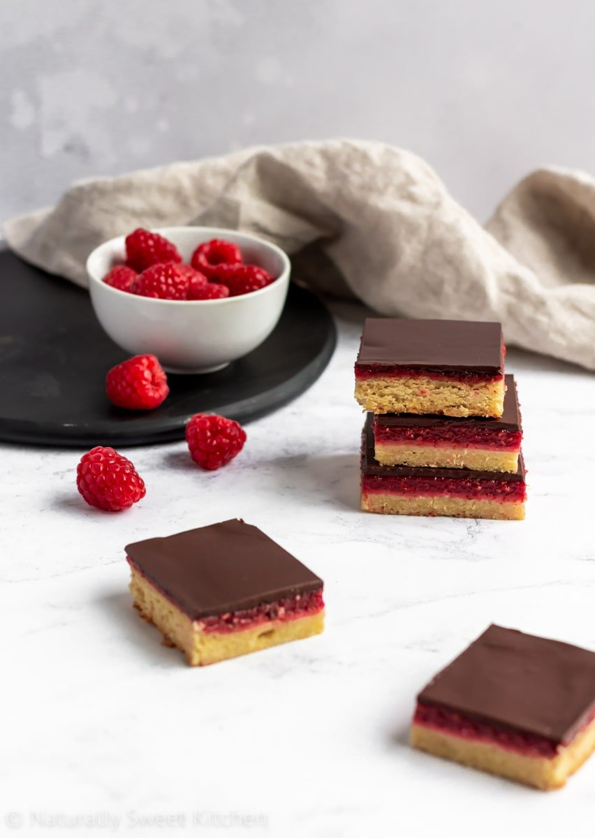 Stacked raspberry bars with naturally sweetened shortbread crusts with a bowl of raspberries behind.