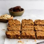 Sugar free apple cinnamon granola bars arranged on white parchment paper with bowls of oats and dates in the background.