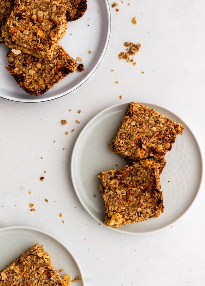 Sugar free granola bars filled with apples and cinnamon on three round plates with crumbles.