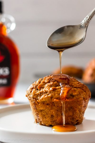 Healthy carrot muffin on a plate being drizzled with pure maple syrup from a vintage spoon.