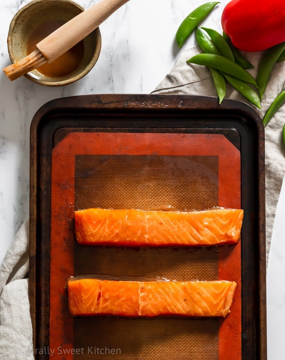 A preparation shot of the maple miso salmon with a bowl of refined sugar free maple miso marinade in the corner.