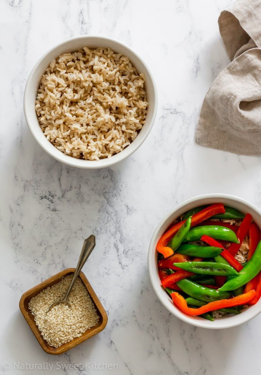 Top down shot of a bowl of rice, a bowl of stir fry red peppers and snap peas, sesame seeds, and a beige napkin.