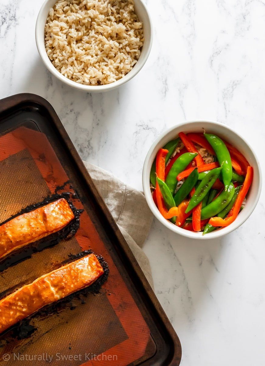 Two pieces of baked salmon on a baking tray next to a bowl of brown rice and a bowl of stir fried veggies.