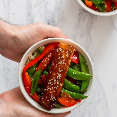 Two hands serving a bowl of maple miso salmon stir fry with sesame seeds on top.