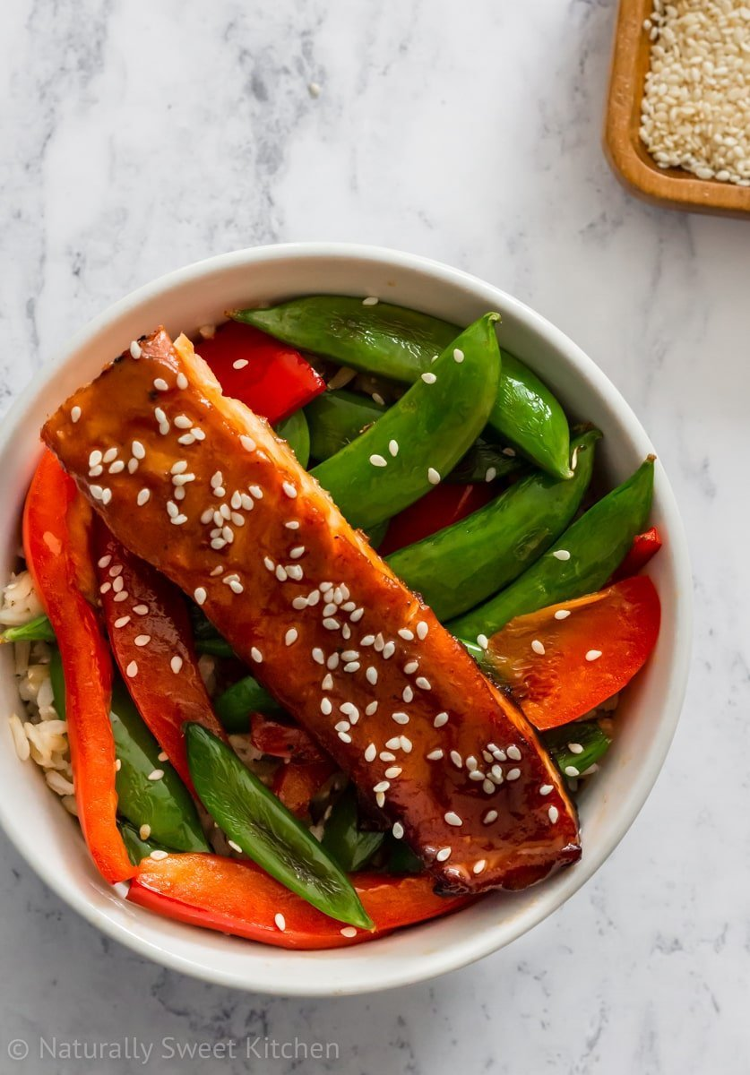 A bowl of healthy salmon with a maple miso glaze, snap peas, red peppers, and brown rice sitting on a marble counter.