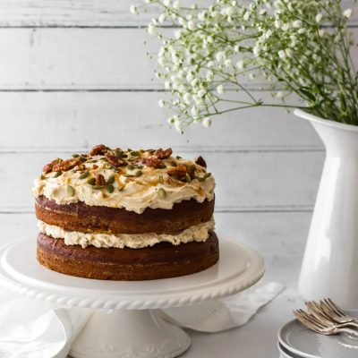 A vegan pumpkin spice cake sat on a white table with a shiplap background. White flowers in a vase and linens around the cake stand.