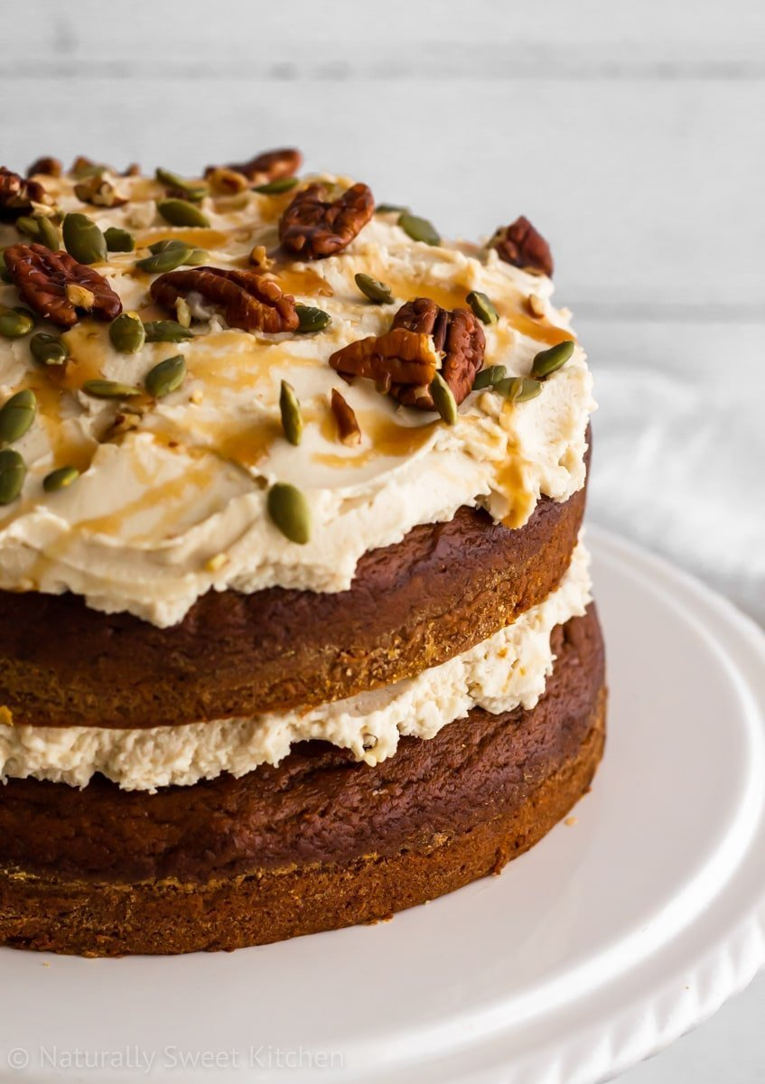 Side shot of a naked refined sugar free cake with white frosting, and nuts and seeds for decoration.