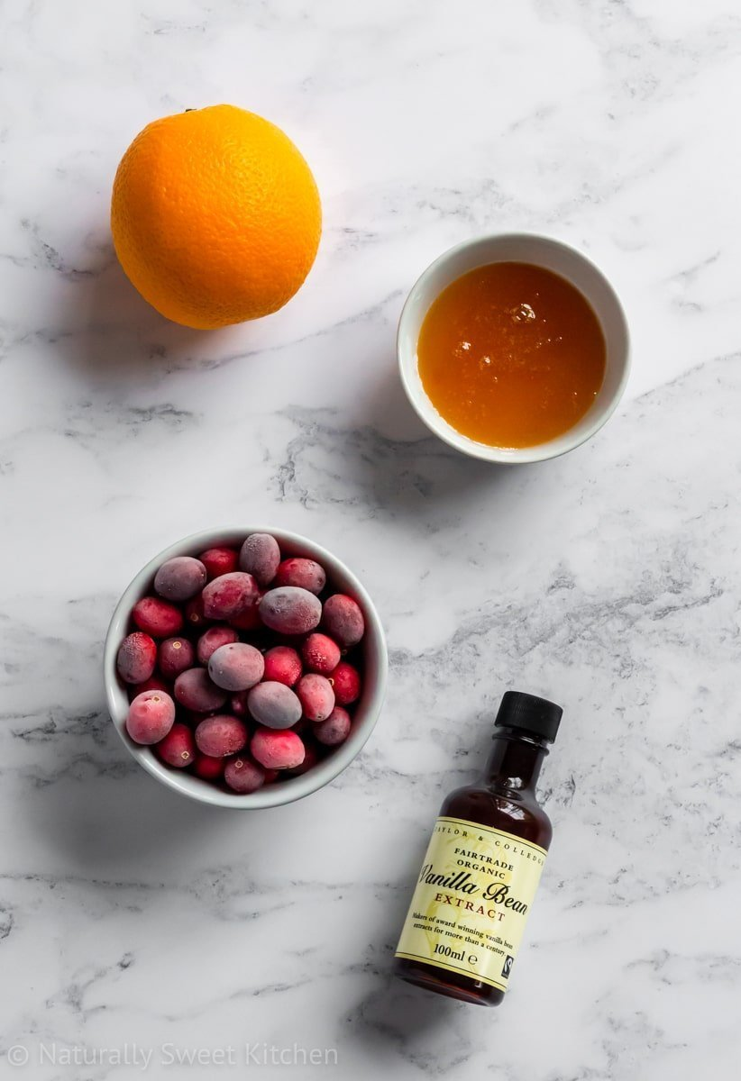 an orange, bowl of honey, bowl of cranberries, and vanilla extract on a marble background.