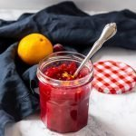 Tangy homemade cranberry sauce in a jar with orange zest and a blue napkin in the background.