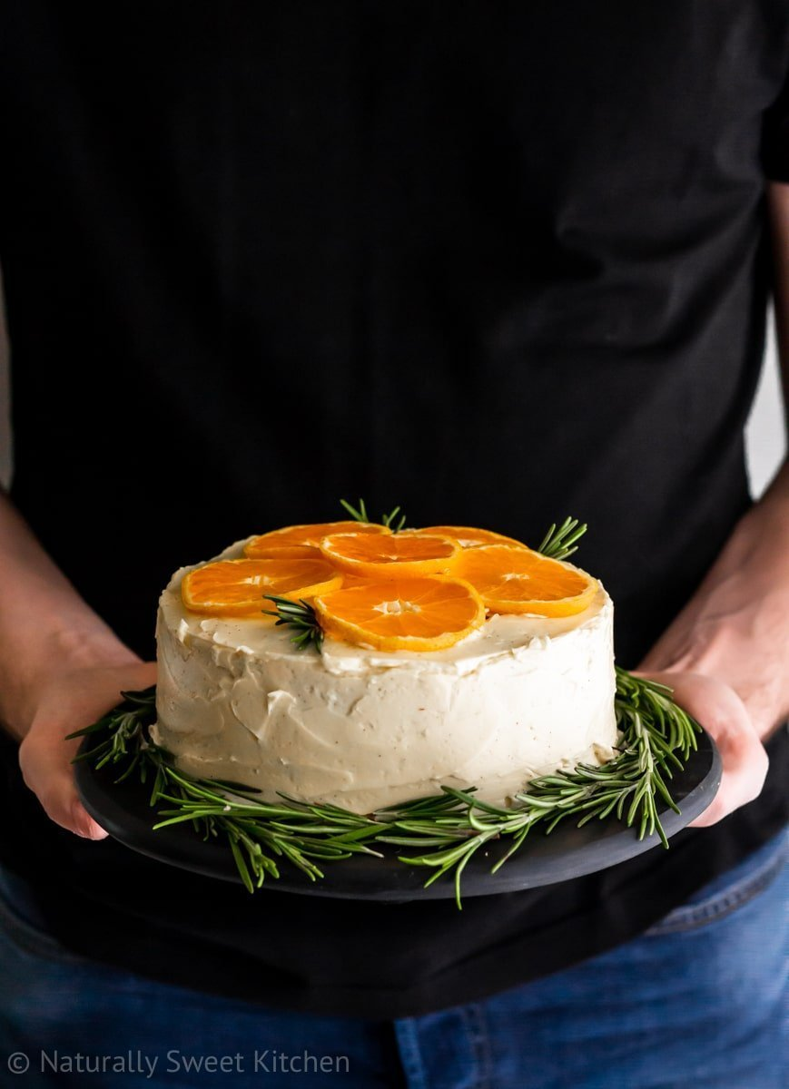 man in a black shirt holding mandarin orange cake topped with fresh fruit and rosemary sprigs