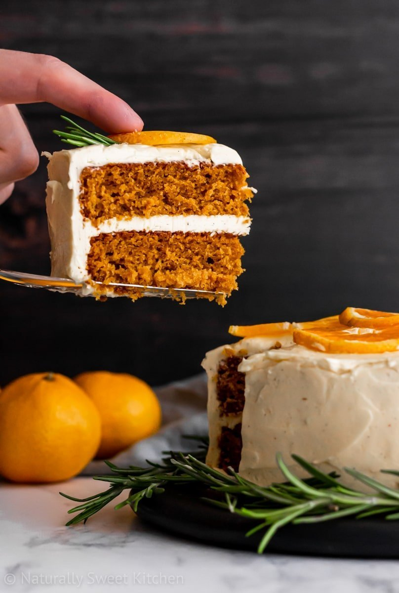 a slice of two layer mandarin orange cake being lifted up with oranges and a brown board in the background.