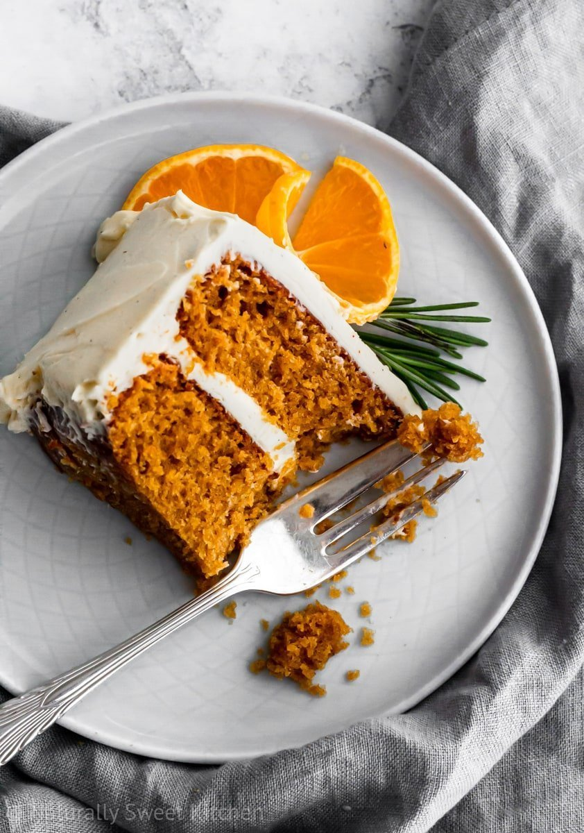 A slice of naturally sweetened mandarin orange cake with a bite taken out with a fork on top of a greyish blue napkin