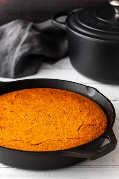 Golden roasted butternut squash cornbread skillet next to a black pot of homemade soup and a grey linen napkin.