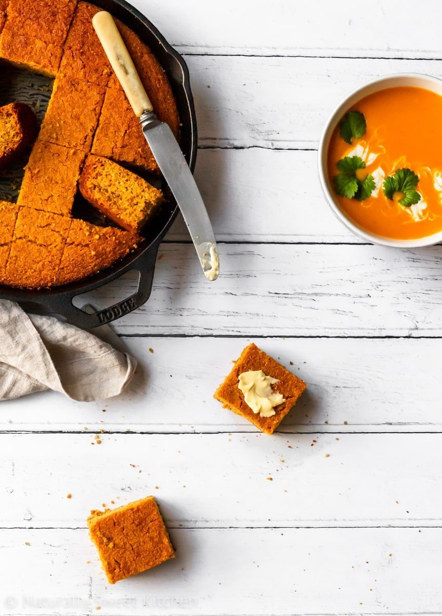 Slices of butternut squash cornbread on a white plank background with a bowl of soup.