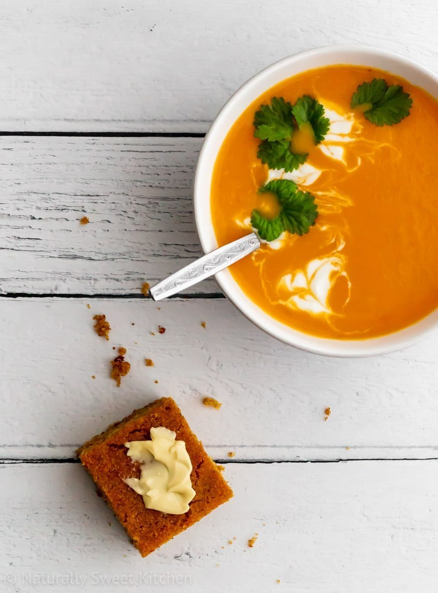 A bowl of butternut squash soup with yogurt and coriander next to a piece of savoury bread on a white wood background.