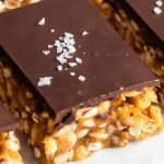 side view of chocolate peanut butter bars with peanuts and crispy cereal