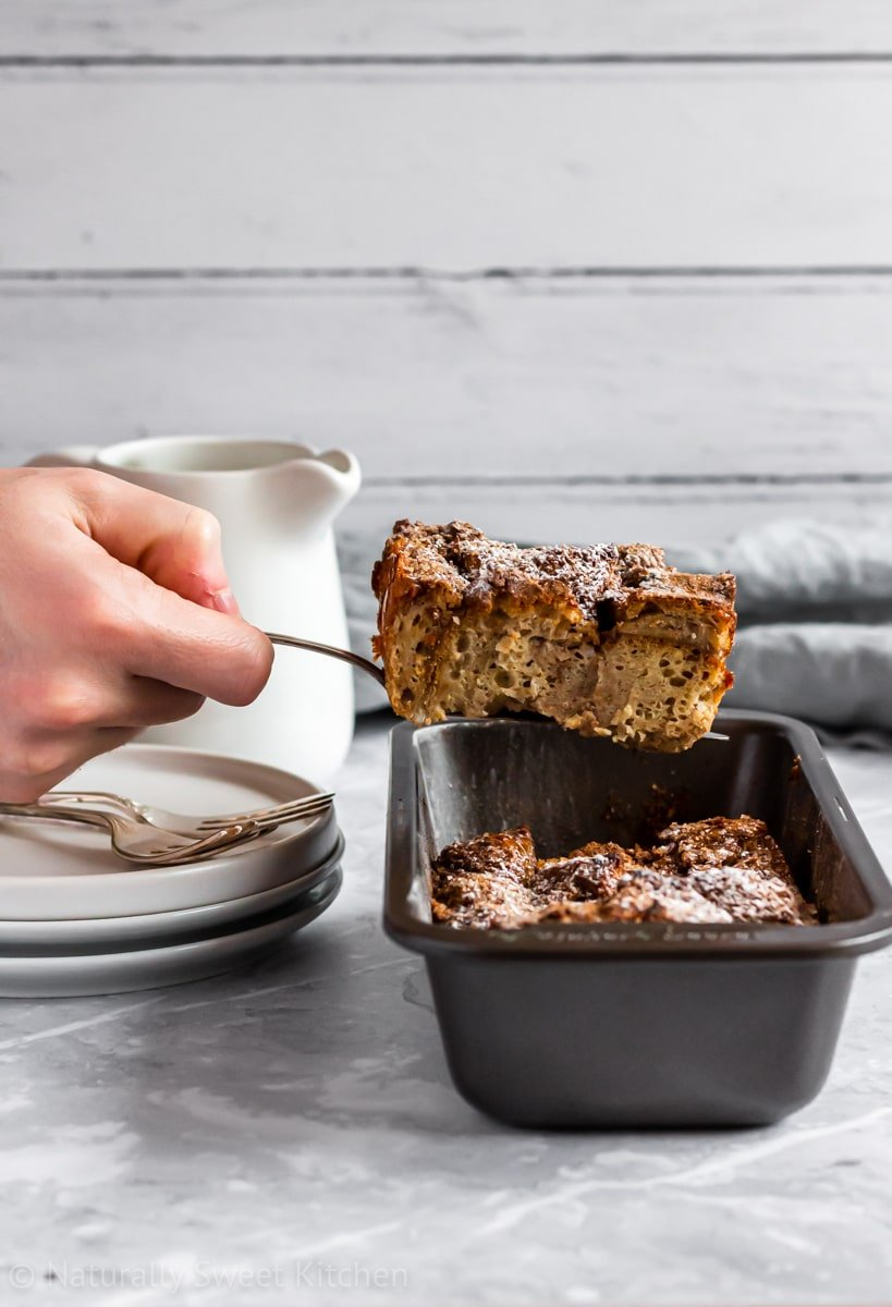 Lifting a serving of chai spiced french toast bake from a grey loaf tin with white plates and a blue-grey napkin in the background.