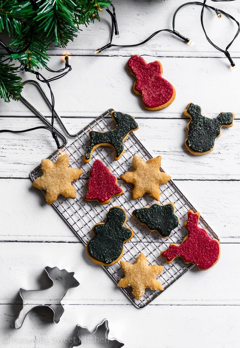 Refined sugar free Christmas sugar cookies on a silver wire rack surrounded by evergreen and Christmas lights