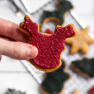 A top down shot of a red sugar cookie being held over a tray of other sugar cookies