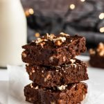 stacked pecan brownies with salted caramel sauce on some wax paper with christmas lights in the background
