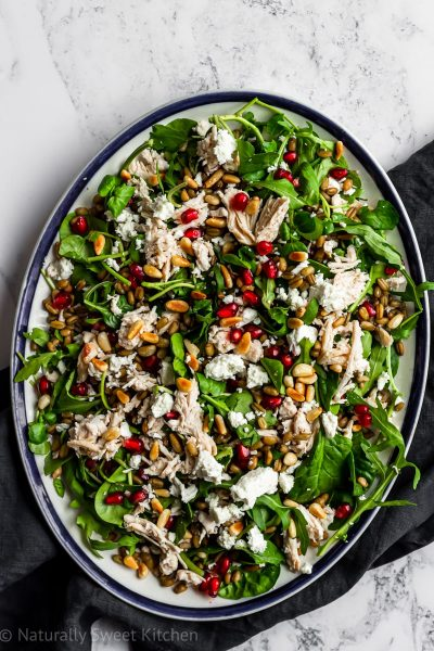 a serving platter of warm pomegranate chicken salad with a grey blue linen on a marble background