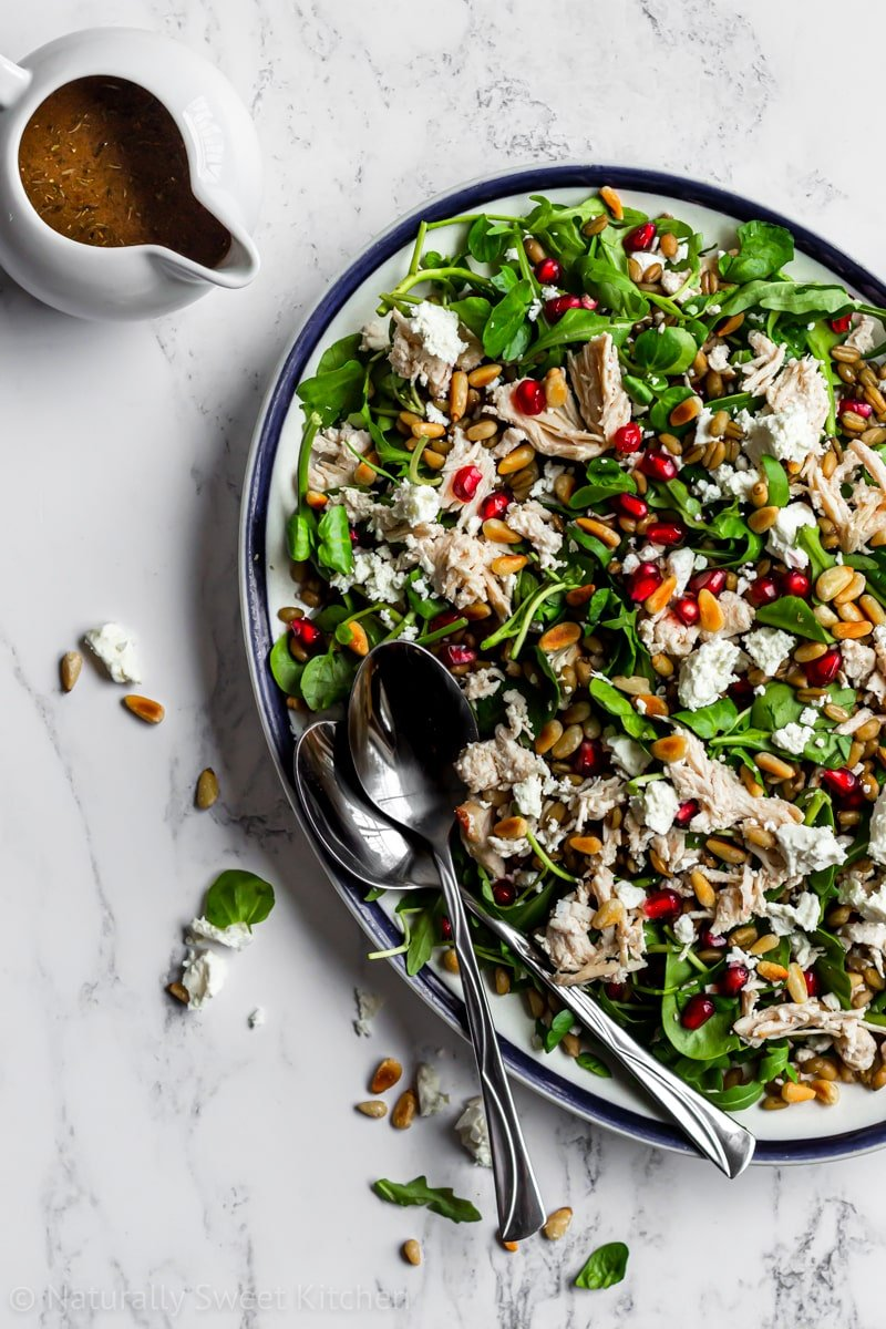 a delicious winter salad recipe on a platter with chicken, grains, and feta cheese and a serving dish of pomegranate balsamic dressing in the corner.