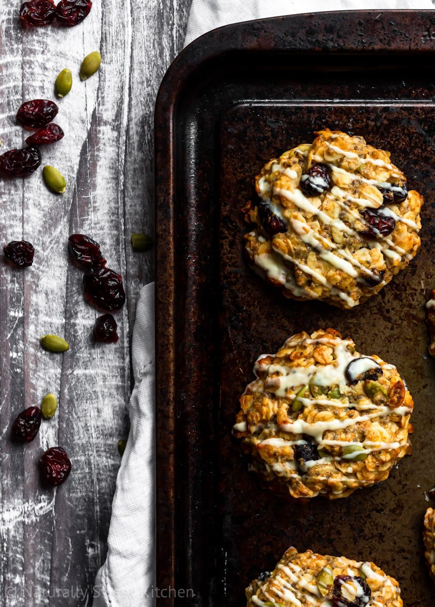 three cranberry almond vegan breakfast cookies on a dark baking tray with cranberries and pumpkin seeds scattered around.