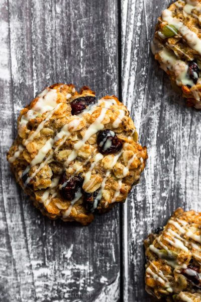dairy-free breakfast cookies with cranberries, pumpkin seeds, and white chocolate drizzle on a grey background