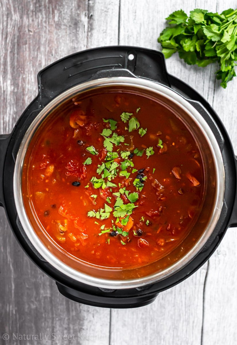 an instant pot full of smoky vegan chili topped with coriander on a grey wooden background