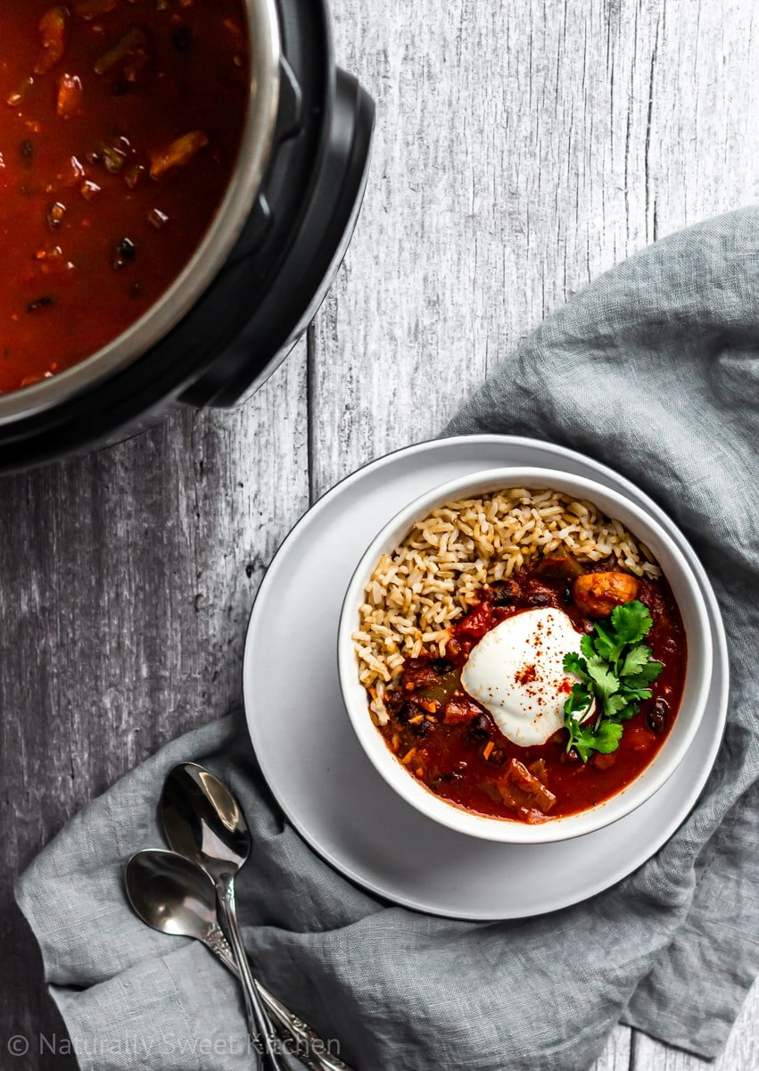 vegan chili and rice in a bowl with the instant pot in the upper corner on a grey wooden background