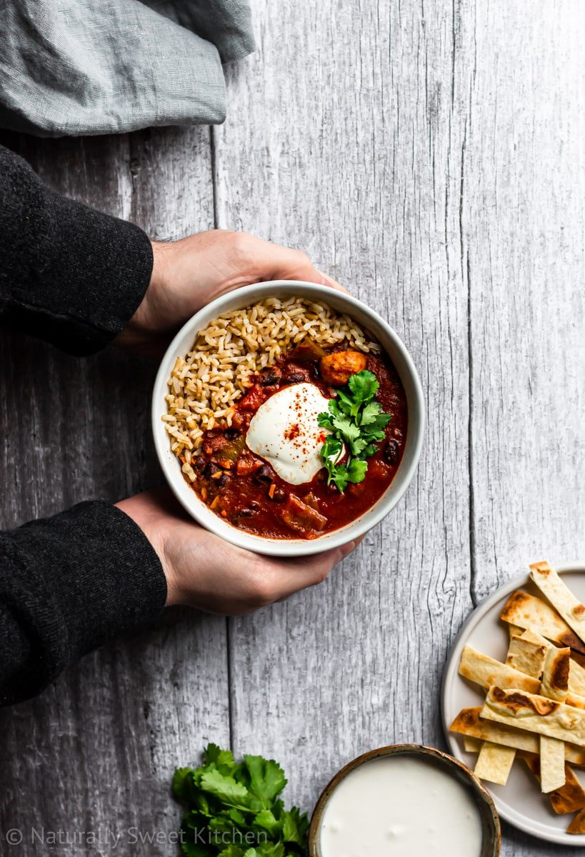 two hands holding a bowl of vegan chili made in the instant pot with toppings on the side of the frame