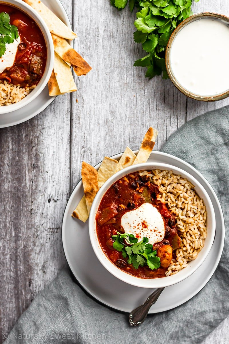 two bowls of instant pot vegan chili on a grey wooden background with a grey linen napkin