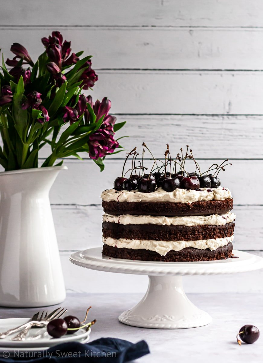 a refined sugar free black forest cake on a white cake stand with a jug of purple flowers in the background.