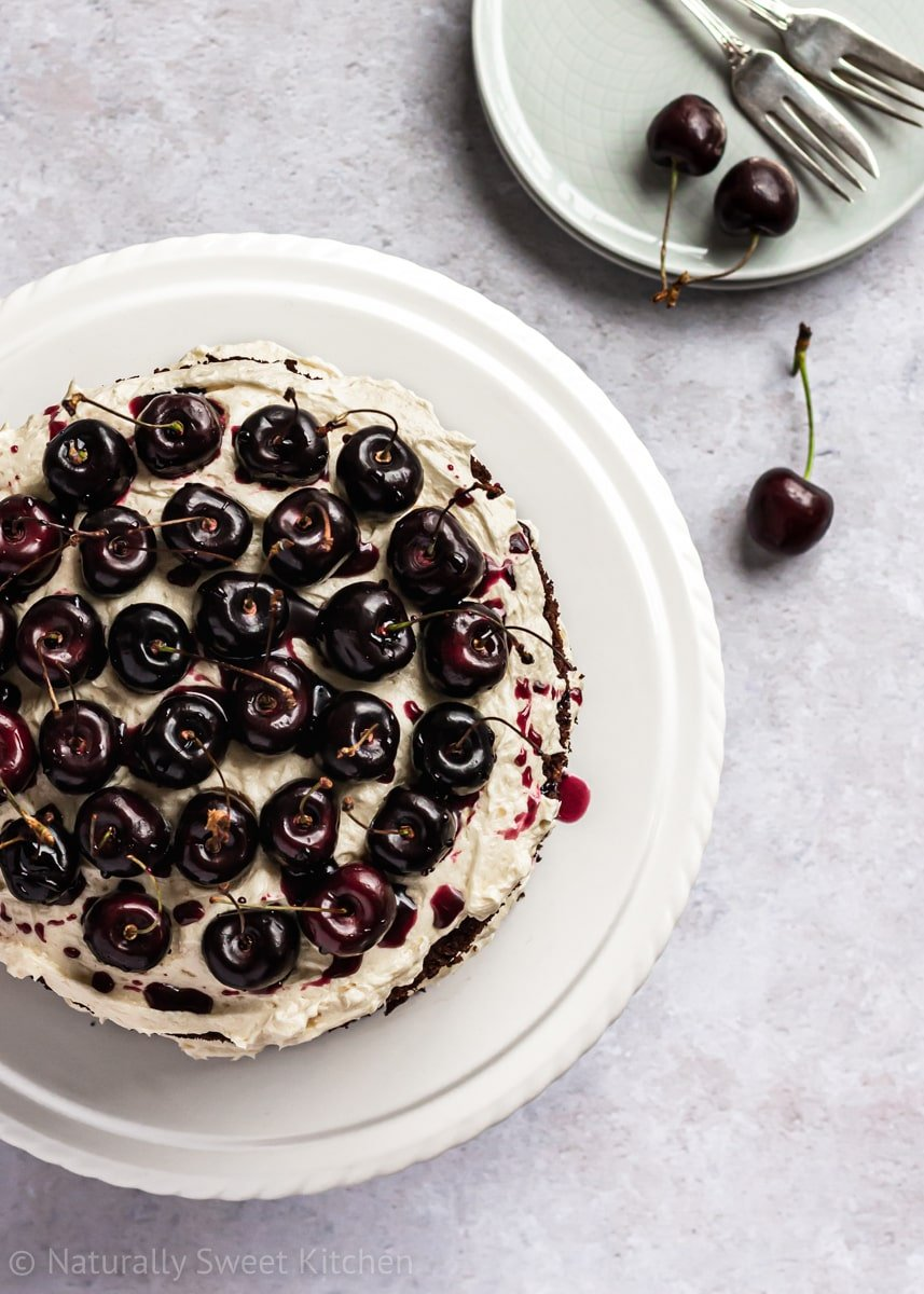 top down shot of a naturally sweetened black forest cake recipe with plates and fresh cherries in the upper right corner