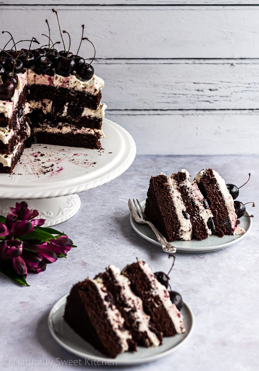two slices of refined sugar free black forest cake on a lavender plasterboard background.