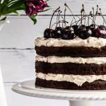 a triple-layer refined sugar free black forest cake topped with fresh cherries