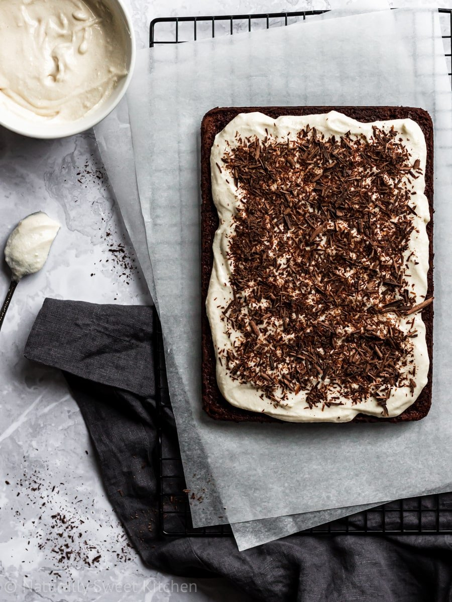 A frosted and chocolate topped naturally sweetened chocolate sheet cake on parchment paper with a grey napkin and bowl of frosting surrounding it.