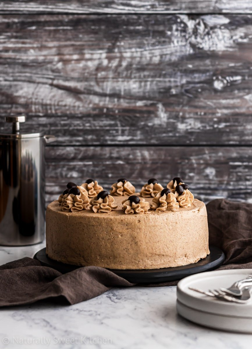 an easy coffee cake recipe with two layers on a black platter with a steel carafe in the background and white plates in the foreground