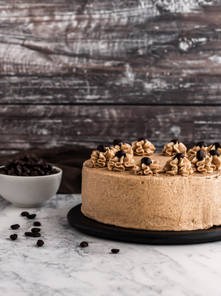 a side-on shot of an easy coffee cake recipe with a bowl of coffee beans for decoration